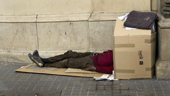 Un mendigo duerme en la Plaza Catalunya_publicada en El País